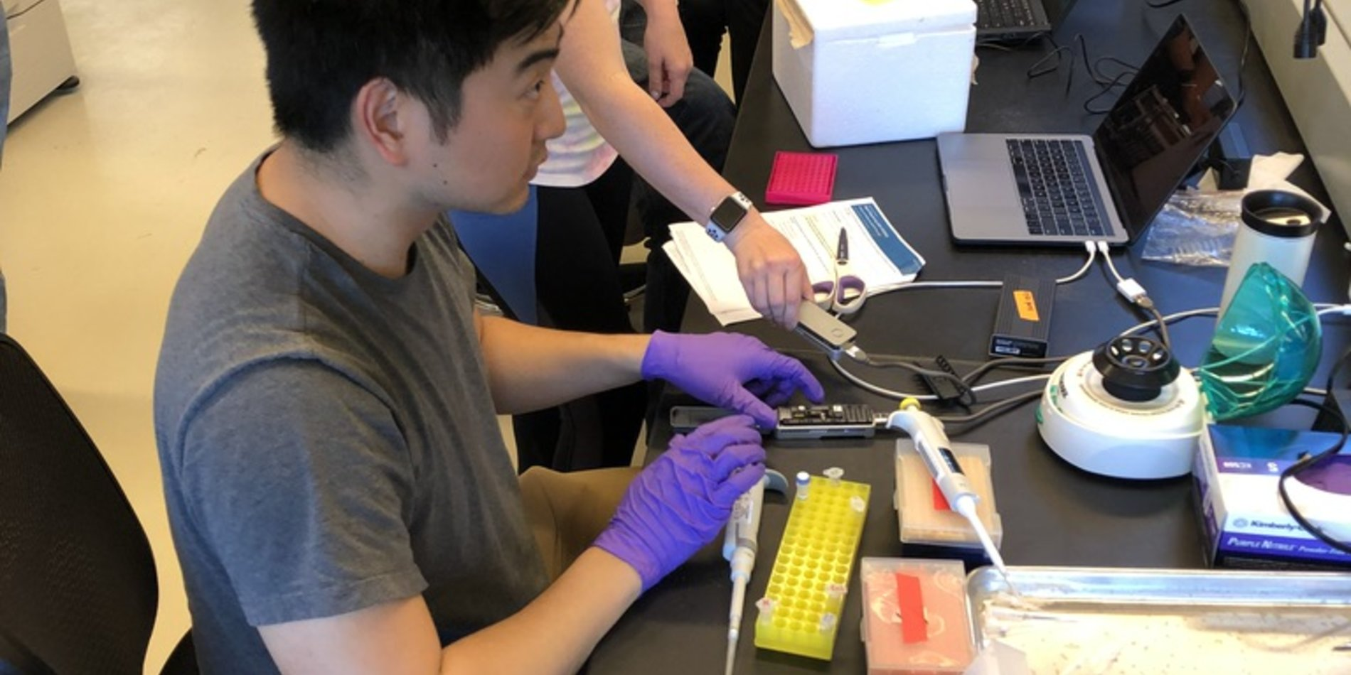 Students using genomics equipment at a lab bench